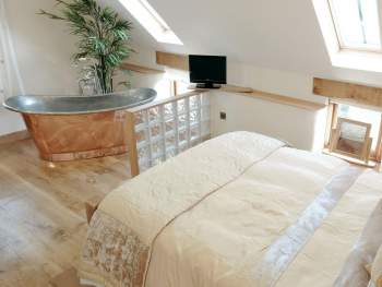 LUXURIOUS BEDROOM FEATURING A COPPER BATEAU BATH