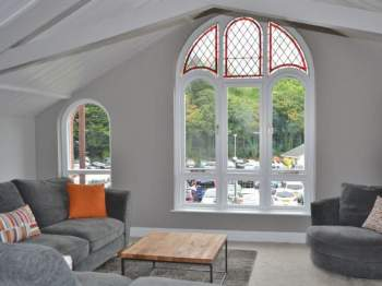 THE HUGE FLOOR TO CEILING ARCHED WINDOW IN THE LVING AREA AFFORDS VIEWS OF THE RIVER
