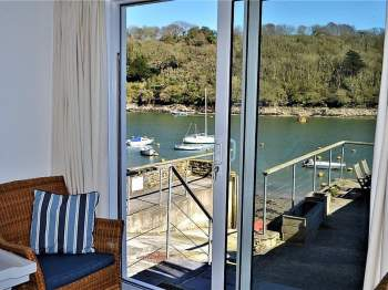 THE SITTING ROOM HAS PATIO DOORS LEADING OUT ONTO A PATIO WITH DELIGHTFUL VIEWS OF THE RIVER
